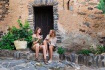 Girls sitting on doorstep and watching photos — Stock Photo