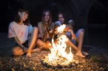 Friends clinking beer bottles at campfire — Stock Photo