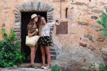 Girls taking selfie at rural building facade — Stock Photo
