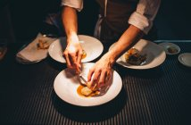 Hands decorating special dishes at restaurant kitchen — Stock Photo