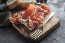 Cured ham with bread and olives — Stock Photo