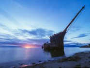 Wrecked ship in sunset time — Stock Photo
