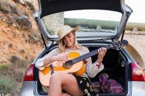 Chica sentada en el baúl del auto y tocar la guitarra - foto de stock