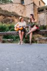 Women with guitar on roadside — Stock Photo