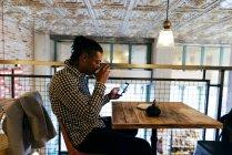 Человек, пить чай и с помощью телефона — стоковое фото