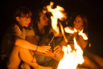 Friends sitting with beer at bonfire — Stock Photo