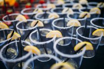 Fila de vasos vacíos con rodajas de limón - foto de stock