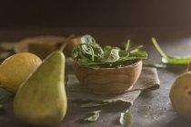 Chiuda sulla vista della ciotola di legno con le foglie di spinaci freschi sul tavolo con pera, limone e kiwi — Foto stock