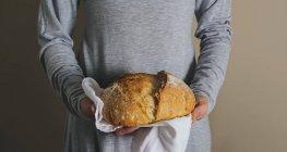 Mãos femininas segurando um pão rústico — Fotografia de Stock