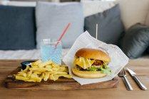 Burger et des frites sur la table en bois. — Photo de stock