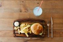 Hamburger et frites sur planche de bois. — Photo de stock