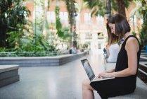 Seitenansicht der junge Brünette Mädchen im schwarzen Kleid sitzt und mit Laptop am Knie — Stockfoto