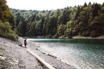 Вид збоку туристичних людина мандрівного стоїть на березі річки в лісі. — стокове фото