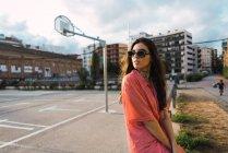 Brunette fille en lunettes de soleil assis sur la clôture à l'aire de jeux de la rue et regardant par-dessus l'épaule loin — Photo de stock