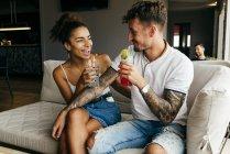 Coppia felice che beve cocktail e si siede sul divano — Foto stock