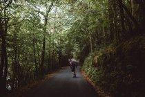 Vista posteriore dell'uomo su skateboard sulla strada asfaltata attraversando la foresta. — Foto stock