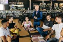 Групи друзів, сидячи в кафе та замовлення до офіціанта — стокове фото
