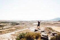 Веселый человек, стоящий на скалы с поднимая руки с камеры вид сзади — стоковое фото