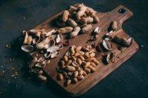 Кучу обстреляли арахис и пилинг на деревянные разделочную доску на темном фоне — стоковое фото