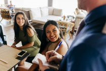 Cheerful people sitting in cafe and ordering — Stock Photo