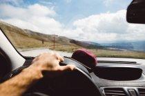 Рука на руле, управляющая машиной на дороге в горах в солнечный день . — стоковое фото