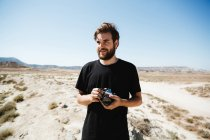 Portrait of bearded man posing with camera on desert — Stock Photo