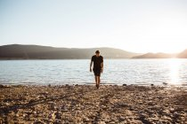 Man walking on sunlit seashore over misty hills on background — Stock Photo