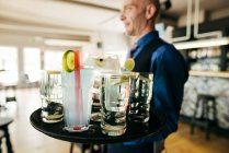 Close up view of drinks on tray carried by waiter — Stock Photo