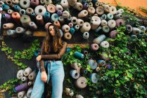 Brunette girl posing at ivy embraced wall with fabric rolls — Stock Photo