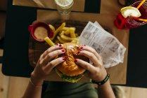 Женские руки культур комплектации гамбургер — стоковое фото