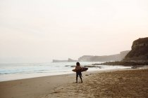 Surfer child walking at seaside with surfboard — Stock Photo