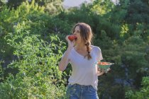 Portrait of girl holding bowl of collected tomatoes in garden and biting one — Stock Photo