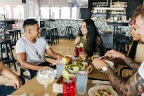 Grupo de alegres amigos jantando juntos no café — Fotografia de Stock