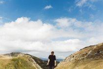 Туристична людина ходьба в сонячної мальовничі гори і, дивлячись — стокове фото