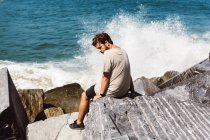 Rear view of man sitting at stones near splashing waves at sea and looking over shoulder — Stock Photo