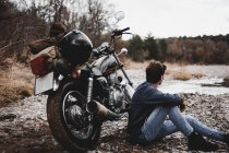 Uomo seduto vicino alla moto parcheggiata e ammirando la riva del fiume di ciottoli — Foto stock