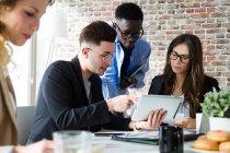 Grupo de personas de negocios que utilizan tabletas durante la lluvia de ideas en la oficina moderna . - foto de stock
