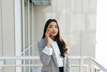 Портрет елегантний бізнес-леді в куртці говорити телефон оголошення фотографіях хтось дивитися вбік — стокове фото