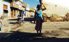 CUBA - AUGUST 27, 2016: Woman standing at street scene and looking away on background of poor district. — Stock Photo