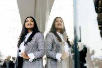 Portrait de faible angle de femme souriante posant près de vitrine — Photo de stock