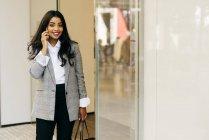 Elegant woman wearing jacket talking phone beside shop window — Stock Photo