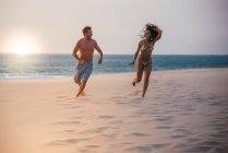 Счастливая пара работает на тропическом пляже романтический и глядя друг на друга — стоковое фото