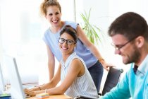 Two smiling women looking at working colleague in modern office. — Stock Photo