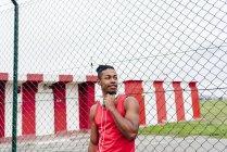 Мужчина опирается на забор и снимает наушники, отводя взгляд в сторону — стоковое фото