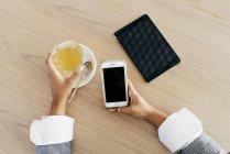 Vista acima das mãos femininas segurando smartphone e xícara de chá verde na mesa — Fotografia de Stock