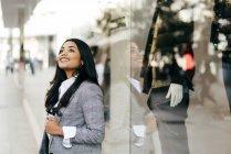 Lächelnde Frau in eleganter Jacke posiert in der Nähe des Schaufensters — Stockfoto
