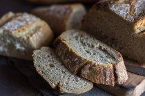 Nahaufnahme hausgemachter Brotscheiben auf rustikalem Brett mit Messer — Stockfoto
