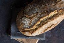 Blick von oben auf selbstgebackenen Brotlaib auf rustikalem Brett — Stockfoto