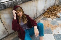 Brunette woman in red jacket sitting on park floor — Stock Photo