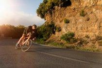 Велосипедиста їзда велосипеді уздовж асфальтована дорога біля глинистий обрив сонячний день. — стокове фото